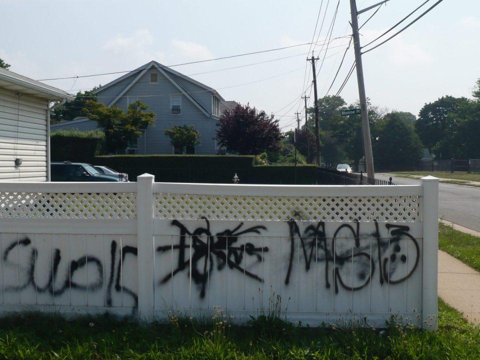 Gang graffiti on a fence in suburban Long Island.