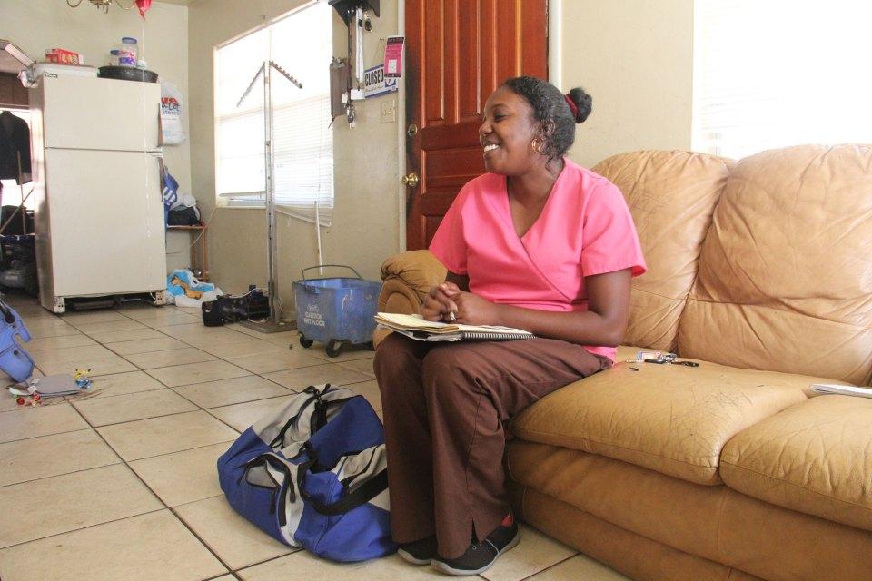Nurse Polita Williams sits in Tiara Jones' living room during a home visit.