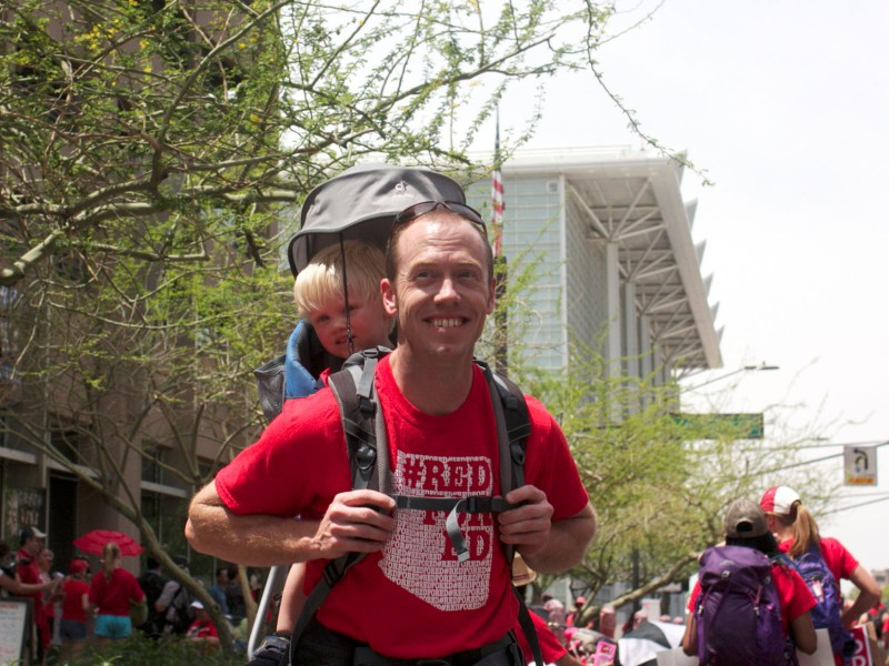 Mitch Askew, a history teacher at Flagstaff High School, marches with his two-year-old son.