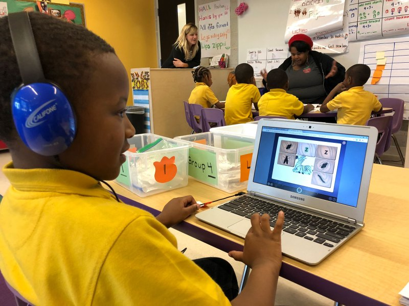 Five-year-old Mykell Robinson practices his reading on the Lexia software while a small group of classmates work with a teacher.