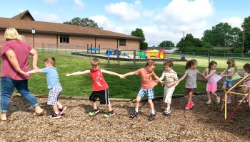 Pre-K students play a game with teaching assistant Johnni Hoene during recess at Zion Lutheran School in Seymour, Indiana.