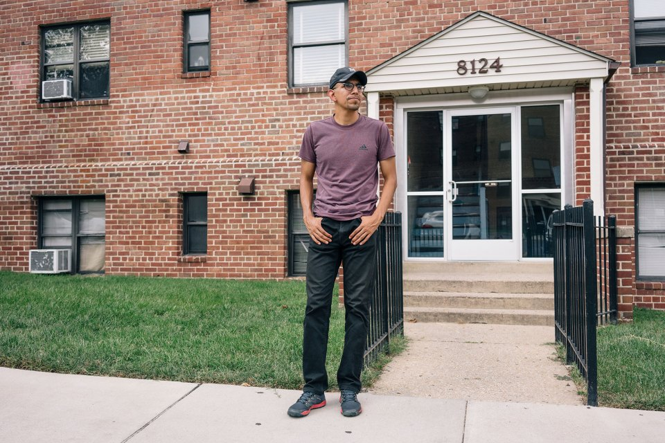 Mario Martinez in front of the apartment building where he grew up in Langley Park, Maryland.