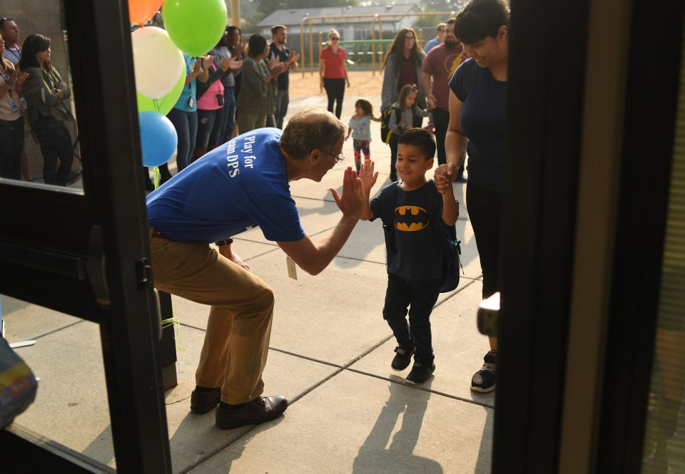 Damian Lopez, 4, gives Denver Public Schools Superintendent Tom Boabserg a high-five as he arrives for the first day of school at Escalante-Biggs Academy on August 20, 2018 in Denver, Colorado.