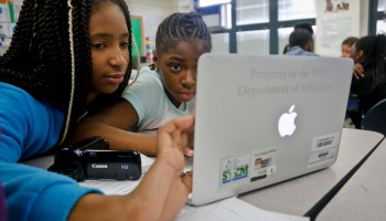 Fifth graders Davonayshia Hollis, left, and Denaya Rippey, review a group entrepreneurial project for a parent-approved music device, developed in a mentorship program, Thursday May 19, 2016, at Brooklyn's P.S. 307 in New York. Startups and established tech companies are providing a crash course in entrepreneurship, sending engineers and designers into public schools to mentor students.