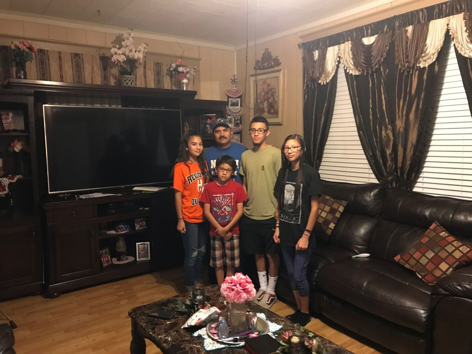 Hermenegildo Rubio stands with his children (from left) Abby, 16, Adam, 10, Danny, 20, and Noemi, 13, in the living room of his Honey Grove home.