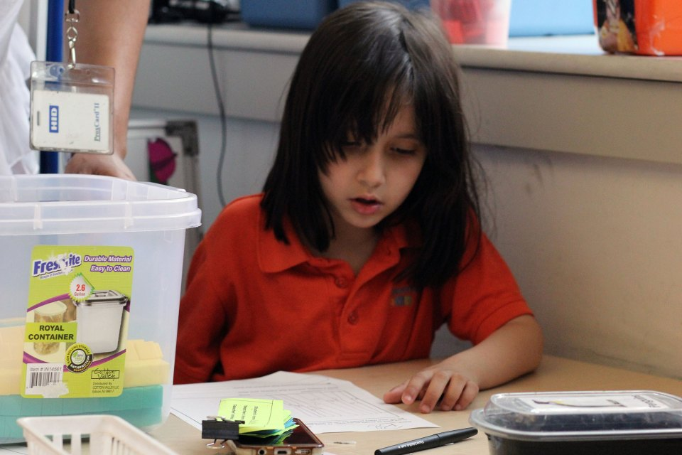 Brandon's sister, Bella, works on a writing project in her first-grade classroom at the Mott Haven Academy Charter School.
