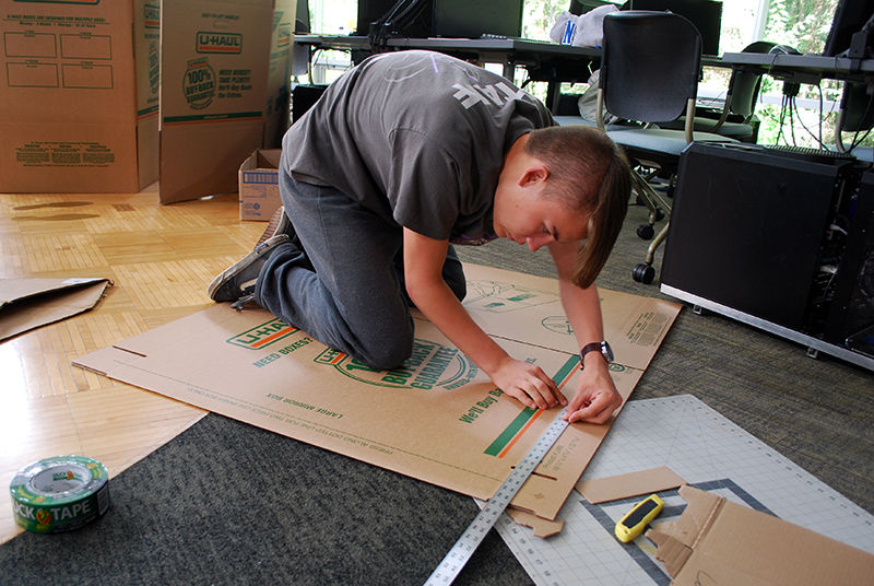 Sam Larson, 15, measures a section of his cardboard canoe during ANSEP's summer Acceleration Academy at the University of Alaska in July 2018.
