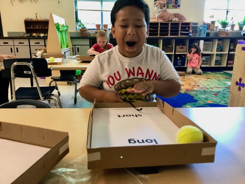 """Malachi Ballinger, 6, laughs at how far he has made his """"pinball"""" travel during a science lesson in his kindergarten classroom in Redmond, Oregon."""