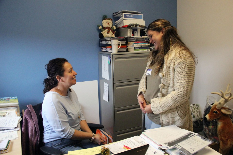 Gloria Kuechenberg, director of family support services at Christopher House, speaks to a mother who has benefited from the school's services.