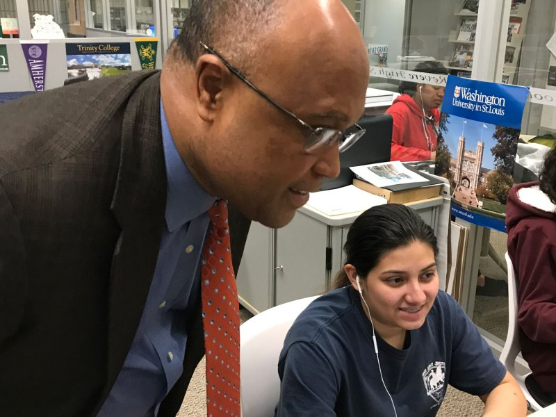 Lourenco Garcia, who earned national attention for his performance as principal at Revere High School, checks in with junior Fatima Vasquez as she works in the school's writing center.