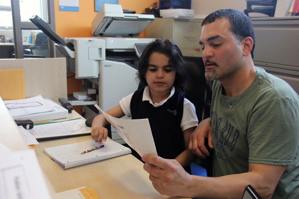 Mariano Agosto helps his daughter Melanie, 7, with homework after school at Christopher House.
