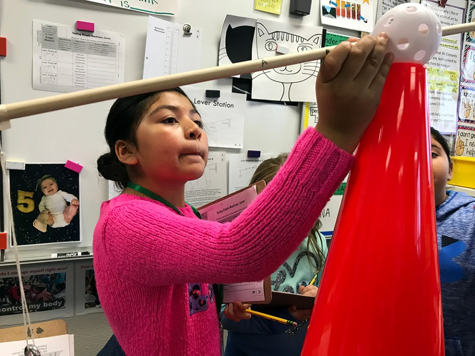 Third-grader Alessandra Gudino Aguilar, 9, adjusts the simple machine, a lever, that she and her classmates are experimenting with during their STEAM enrichment class at Pioneer Elementary School in Quincy, Washington.
