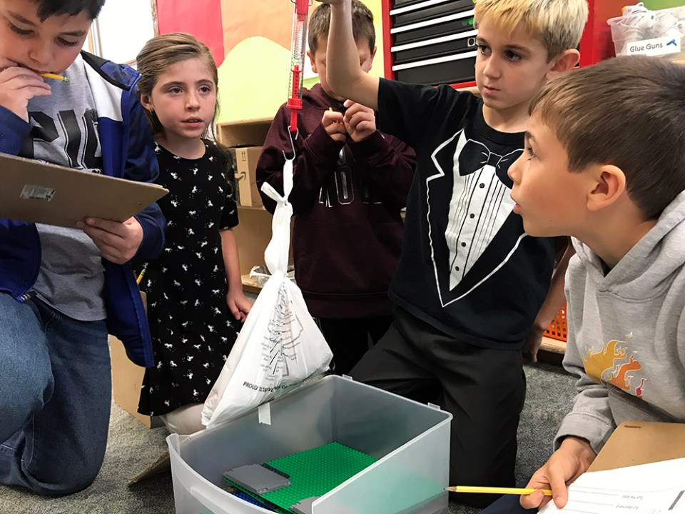 During their STEAM enrichment class at Pioneer Elementary School in Quincy, Washington, Emmett Bogle, 9, pulls a bag of potatoes up a ramp, while classmates Madilynn Mendoz-Felix, 8, and Mason Duran, 9, check the force reading and Hector Quintero-Ruesga, 9, records the result.