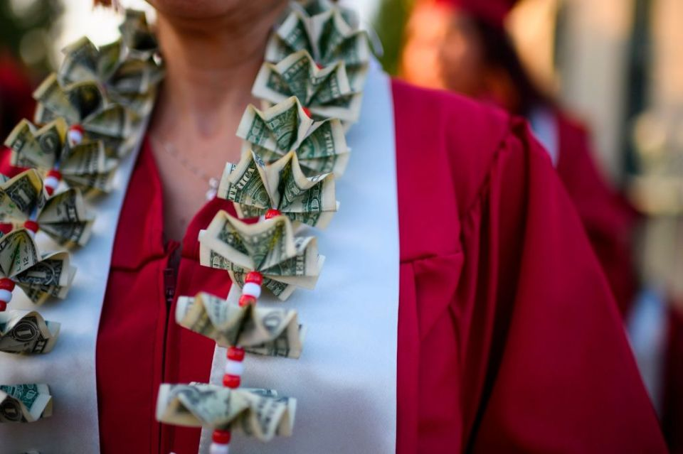 A graduating student wears a money lei, a necklace made of US dollar bills, at the Pasadena City College graduation ceremony, June 14, in Pasadena, California. With 45 million borrowers owing $1.5 trillion, the student debt crisis in the United States has exploded in recent years and has become a key electoral issue in the run-up to the 2020 presidential elections.