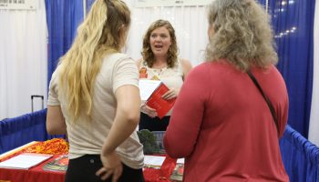 """Erin Nelson, a recruiter from Iowa State University, talks with Emily Behrendsen, 17, and her mother, Diana, at a college fair in Pasadena, California. Emily's older brother is going to Alaska for college, Diana Behrendsen says. """"I just feel like they need to go where they can thrive and be happy."""""""