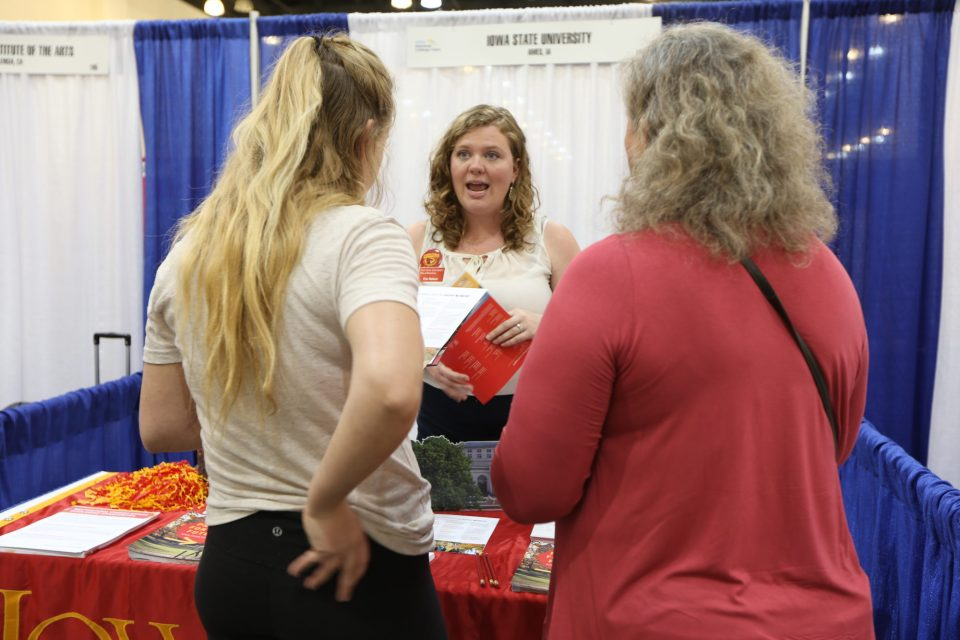 "Erin Nelson, a recruiter from Iowa State University, talks with Emily Behrendsen, 17, and her mother, Diana, at a college fair in Pasadena, California. Emily's older brother is going to Alaska for college, Diana Behrendsen says. ""I just feel like they need to go where they can thrive and be happy."""