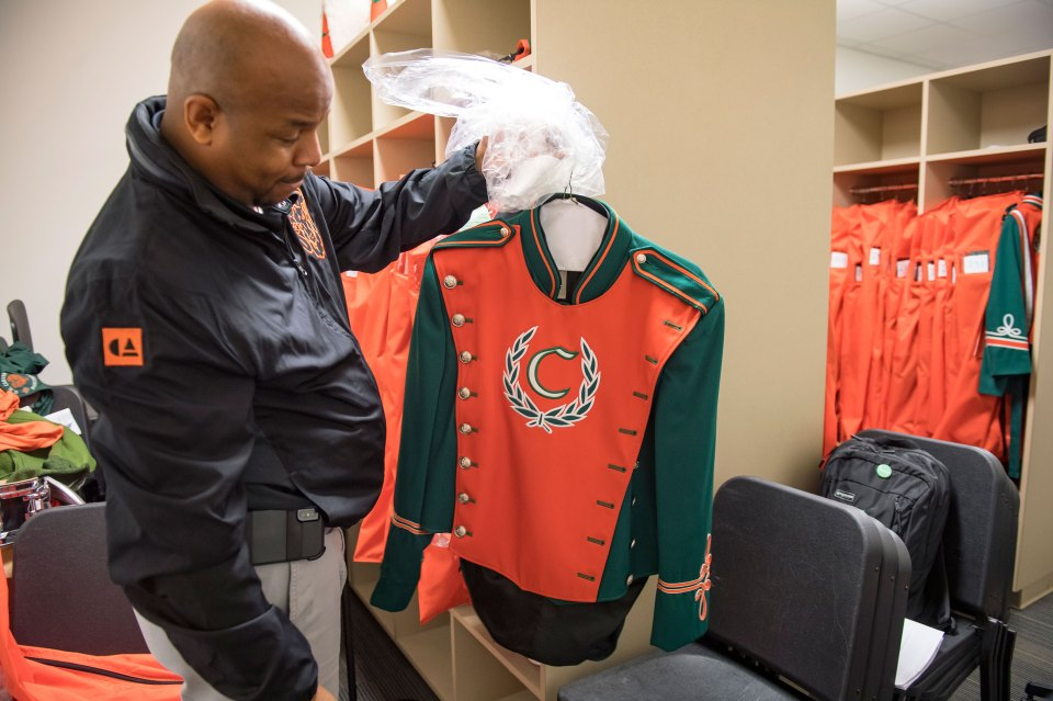 Assistant band director Patrick Williams shows a drum major's marching uniform. George Washington Carver School band in New Orleans gets ready for Mardi Gras in February 2019.