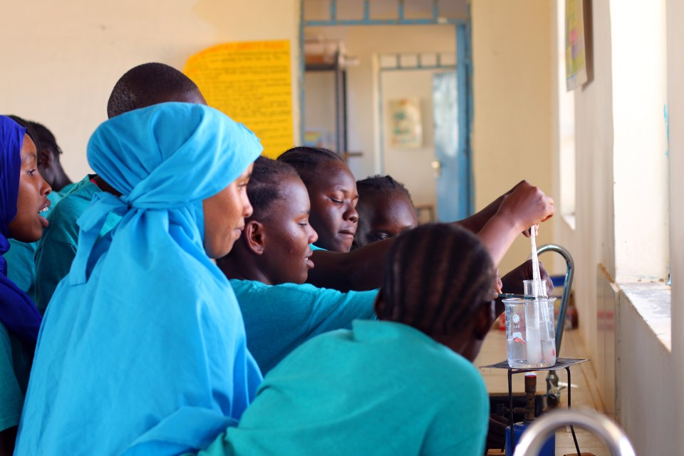 Students at Morneau Shepell Secondary School for Girls crowd around a Bunsen burner during a chemistry lab. The school spends $700 per pupil each year—about $550 more than other secondary schools in the camp— yet still doesn't have enough textbooks and supplies to go around.
