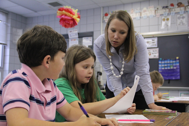 Laurie Langford, a second grade teacher at West Defuniak Elementary, helps two students look for evidence in a reading passage about public sector jobs. (Photo: Jackie Mader)