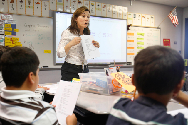 Second-grade teacher Vickie Boudouris goes over a work sheet her students were doing in an English Language Learner summer school class at the Cordova Villa Elementary School, Wednesday, June 12, 2013 in Rancho Cordova, Calif. File photo. (AP Photo/Rich Pedroncelli)