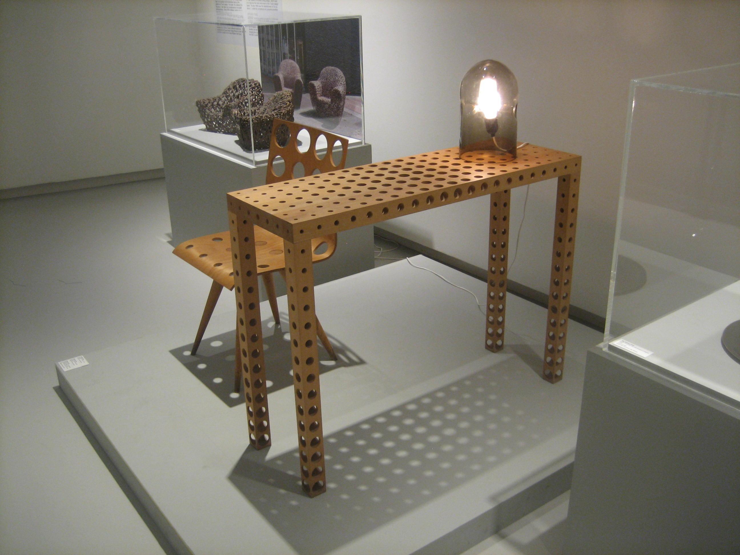 Gijs Bakker, Chair with Holes no. 2, 1991, Fruit Table with Holes, 1993 en Glass Lamp, 1978. Toen Emmy nu Gijs. Collectie Design Museum Den Bosch, tentoonstelling, vitrine, tafel, lamp, stoel, hout, glas