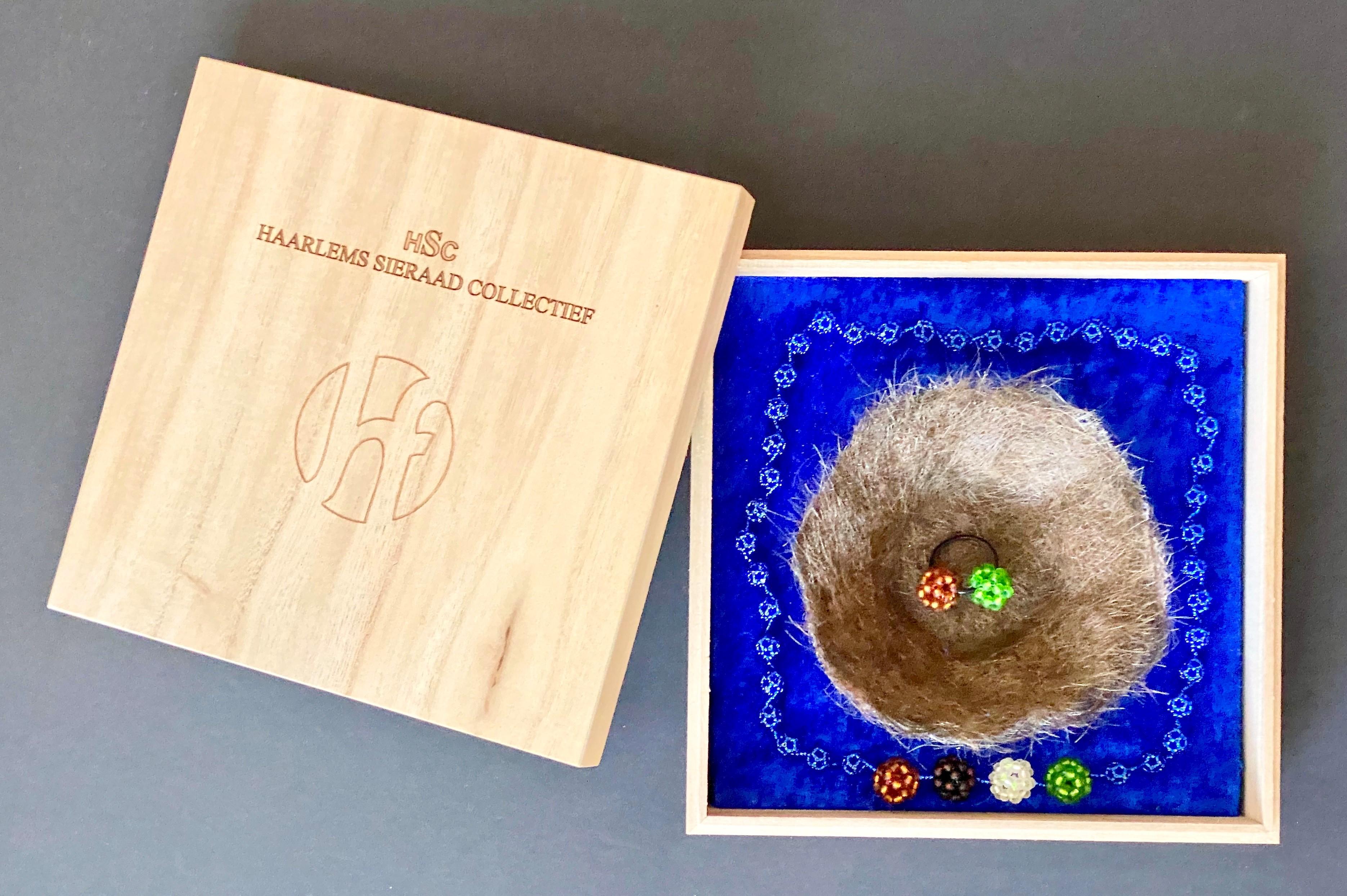 """Hilde Foks, halssieraad/ring/object, 2018. Set bestaande uit een collier van 40 kleine glazen kraaltjes en met 4 grotere. Tevens een nestje gemodelleerd van het eigen haar (!) van Margriet en Michel waarin een """"tweeling-ring"""" (een verwijzing naar onze tweeling). Collectie Margriet Blom & Michel Krechting. Foto Michel Krechting"""
