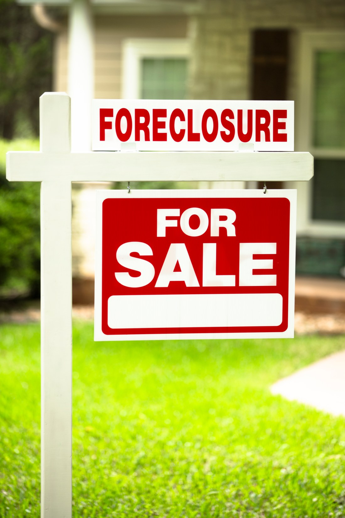"Red and white ""Foreclosure, Home for Sale"" sign in front of a stone, wood house that is for sale and is being foreclosed upon by a financial institution. Green grass and bushes indicate the spring or summer season. Front porch and windows in background. Economic depression, recession, bankruptcy concepts."