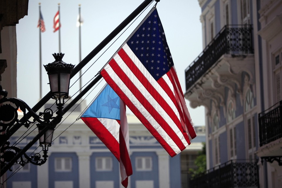 FILE - In this June 29, 2015 file photo, U.S. and Puerto Rico flags hang outside the governor's mansion in Old San Juan, Puerto Rico. Puerto Rico's power company said Wednesday, Sept. 2, 2015 it reached an agreement with a group of bondholders to restructure the troubled agency, providing some relief to investors who believed it soon would go bankrupt. The bondholders hold about 35 percent of the power company's bonds and represents hedge funds and municipal bond investors. (AP Photo/Ricardo Arduengo, File)