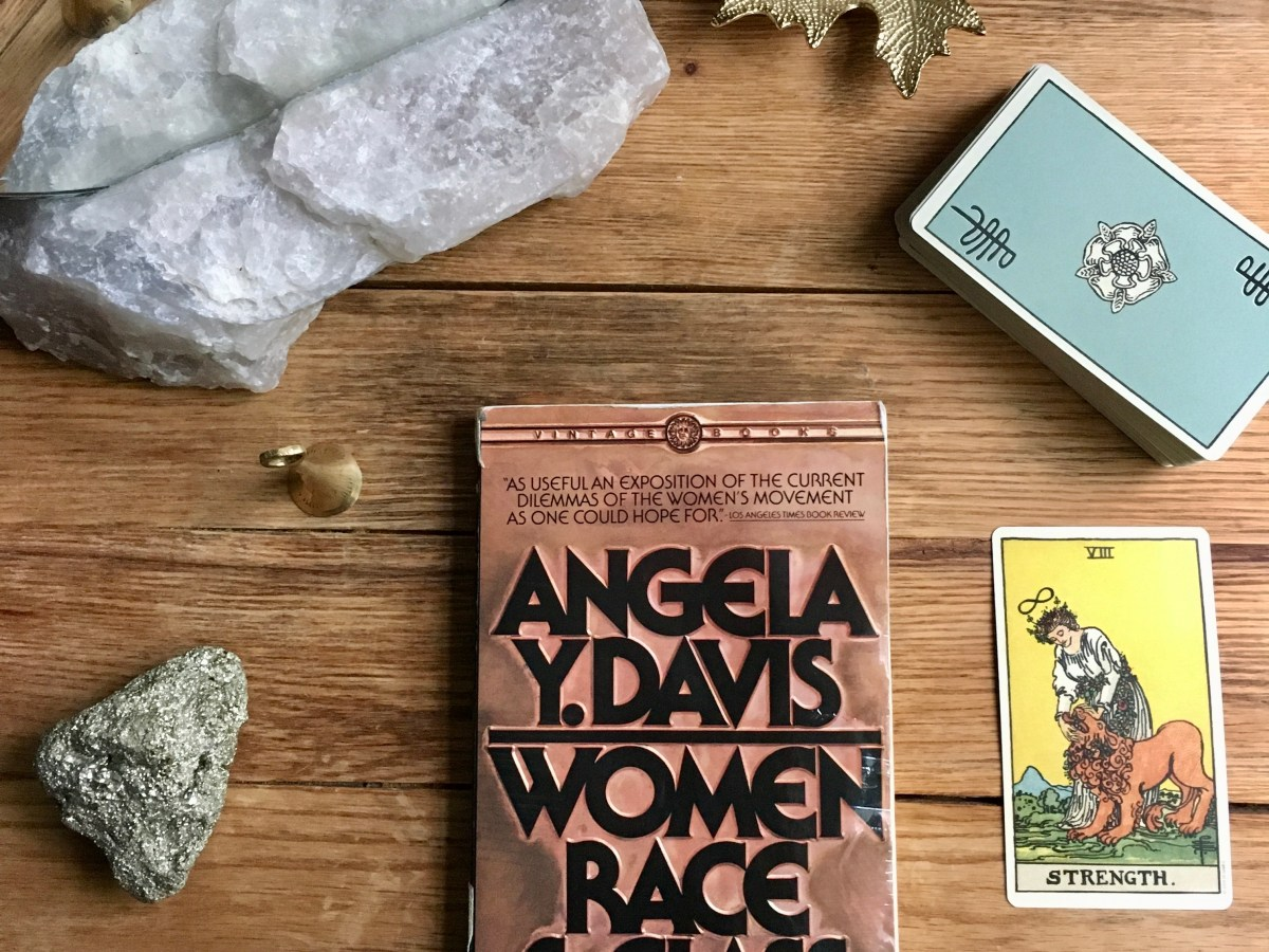 "Paperback copy of Angela Y. Davis' ""Women, Race, & Class"" surrounded by pyrite crystal, mirror, leaf-shaped candle holder, tarot card for strength, and deck of tarot cards."