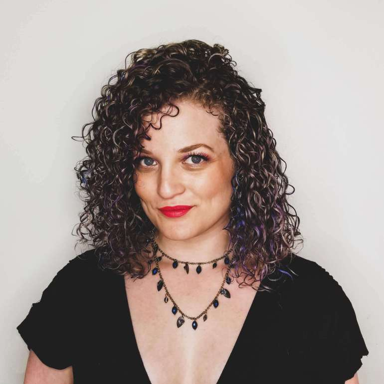 Photo of Rachael Rose, a white curly haired woman with bright lipstick looking at the camera.