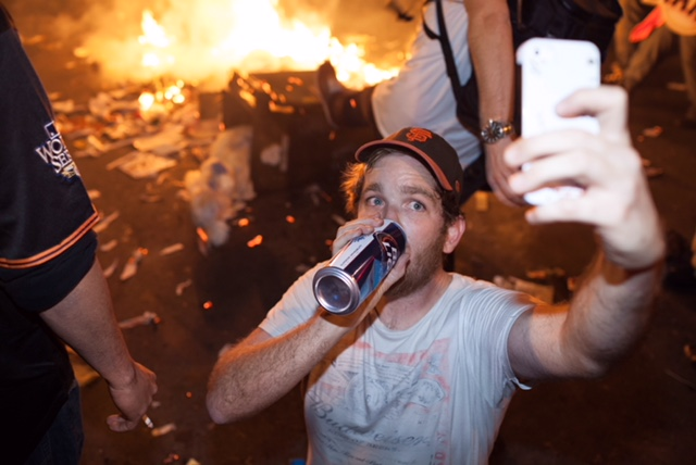 Guy drinking beer and taking selfie