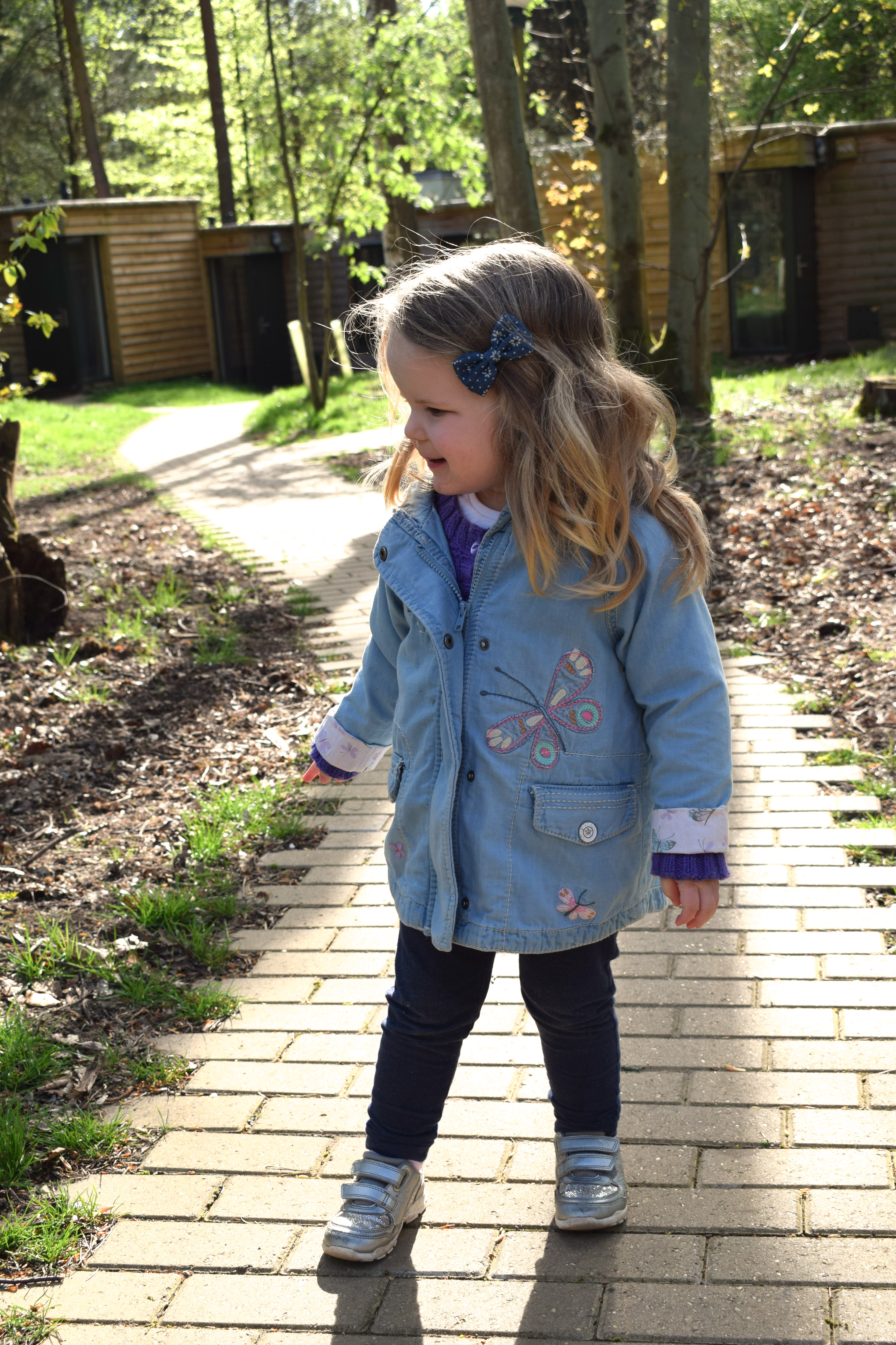 two year old girl standing on a path at Center Parcs Elveden Forest