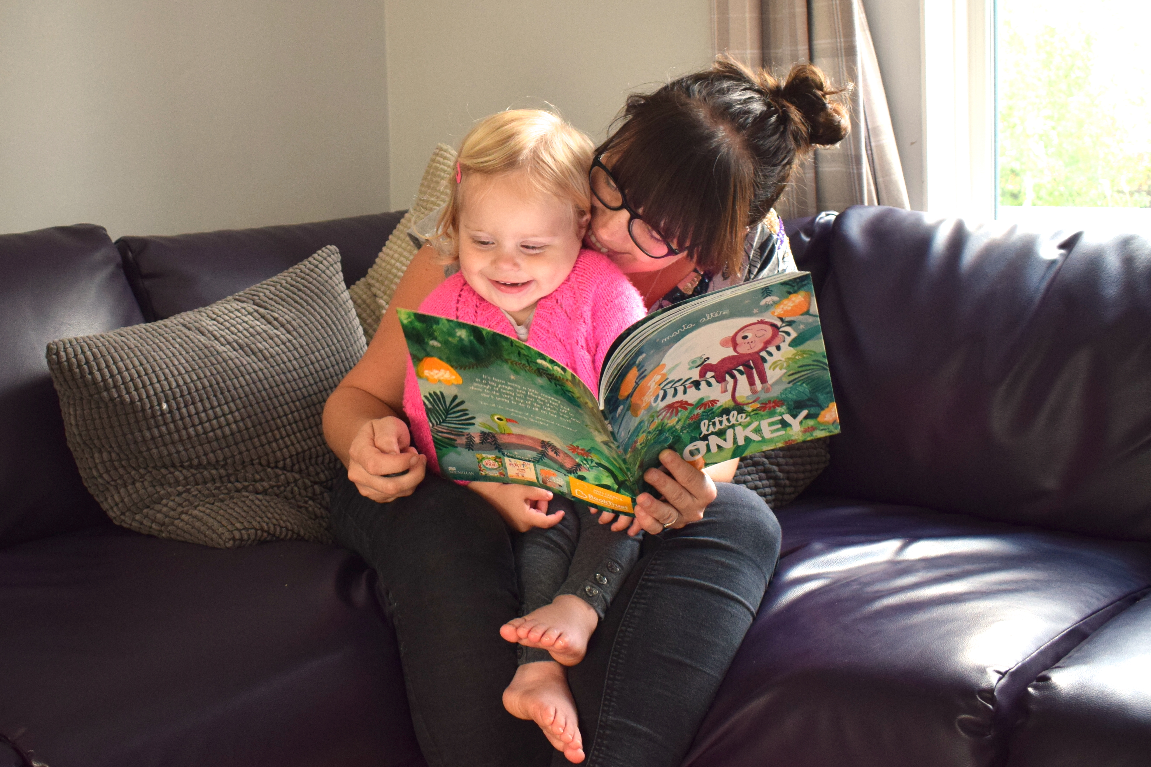 mother laughing with one year old on her lap, during time to read