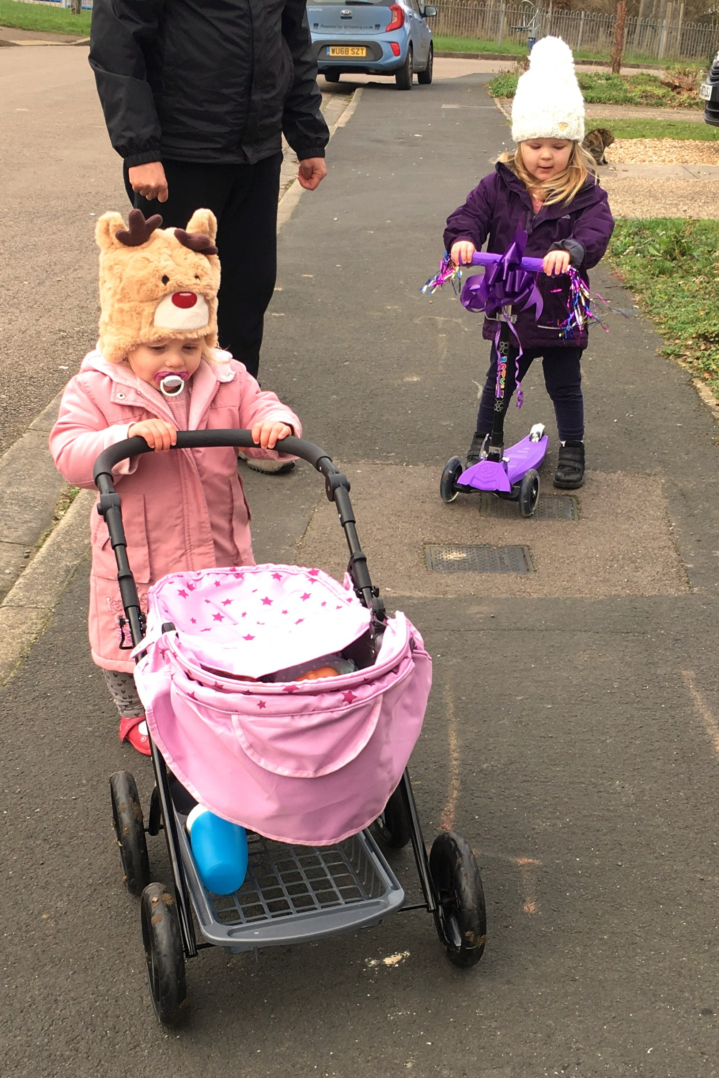 two sisters, one pushing a dolls pram, and one on a scooter, going out for a walk with their dad