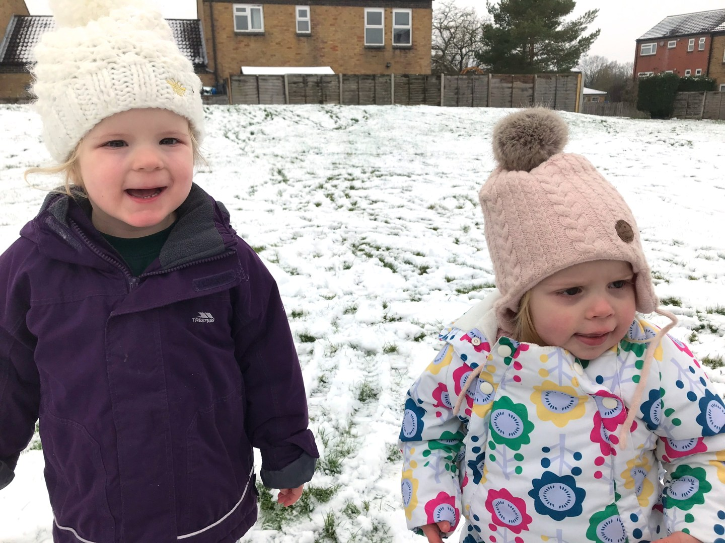 Two sisters in bobble hats, standing in a snowy field