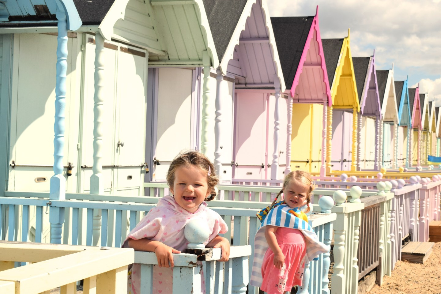 two little girls on the decking of a beach hut, leaning on the balustrade