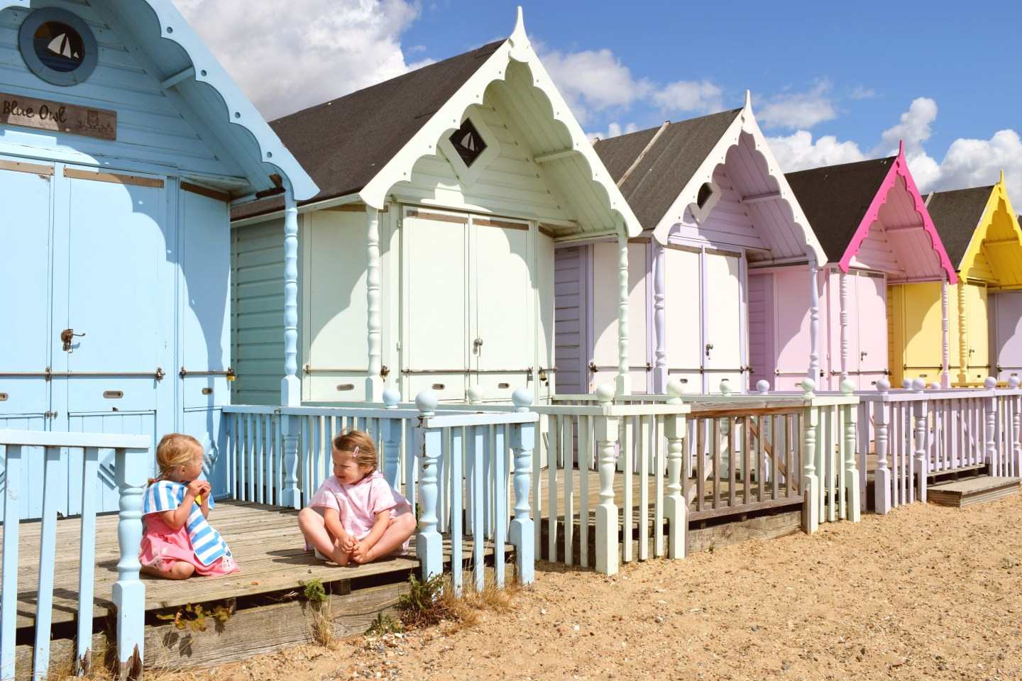 two little sisters sitting next to one another on the decking of a beach hut