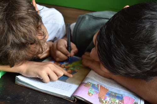 two boys looking at a school book together