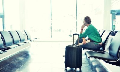 woman sitting in empty airport with luggage