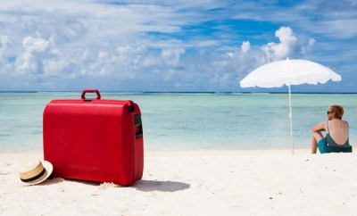 beach vacation suitcase in sand