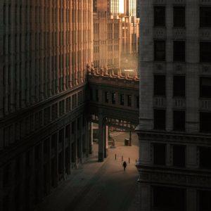 person walking on street between buildings