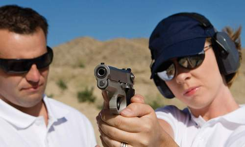 A son holding a gun, while receiving gun safety training from his father