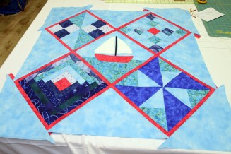 The five main blocks all pieced together with the red sashing and the setting and corner triangles, just waiting for the borders and border star blocks to be pieced on.