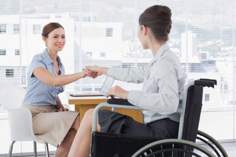 Disability Meeting - Businesswoman shaking hands with disabled colleague at desk in o