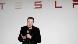 Elon Musk auf Bühne vor Tesla-Schriftzug