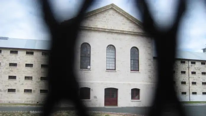 Prison building viewed through a metal fence