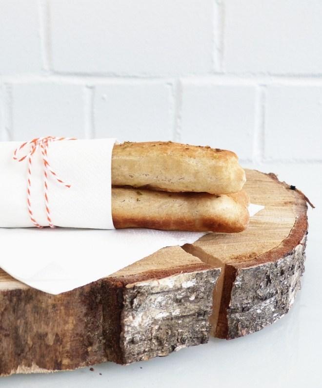 Drei Brotsticks mit Serviette und Bäckergarn