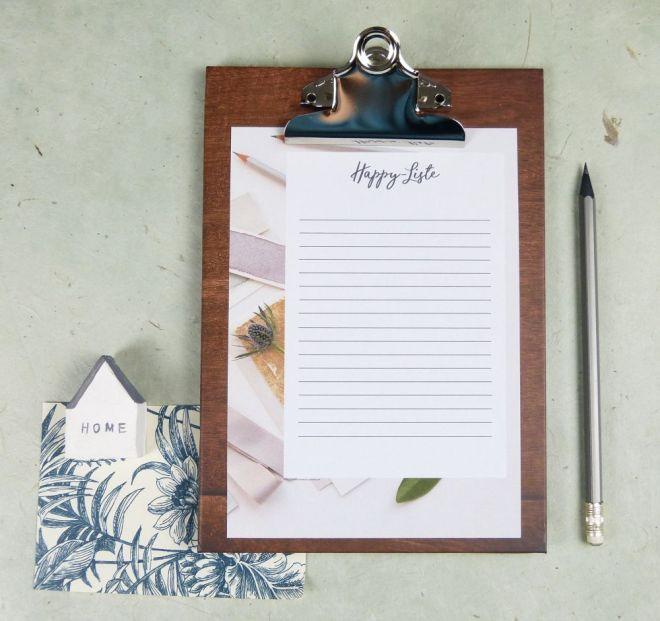 Klemmbrett mit Happy Liste und Bleistift