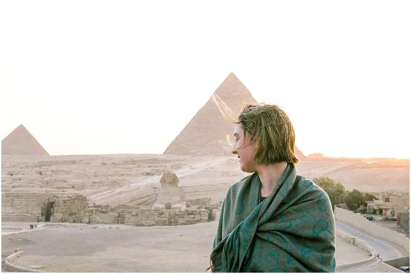 Woman in shawl at Pyramids of Giza in Cairo Egypt Sphinx