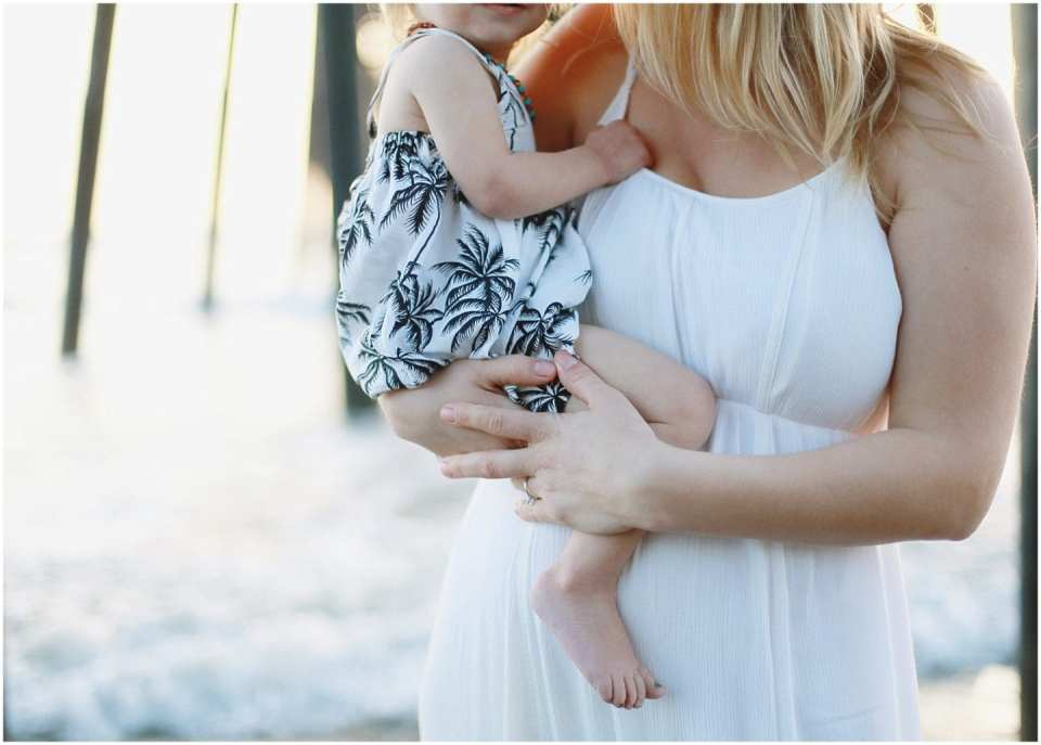 mom and baby with a white dress at pier beach portrait session